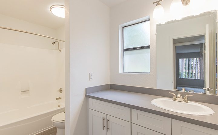 Bathroom with lighted mirrors next to shower at the Reserve at South Coast apartments in Santa Ana