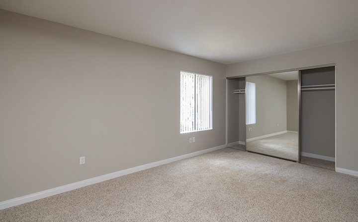 Large unfurnished bedroom at Adagio at South Coast apartments with mirrored walk-in closet doors