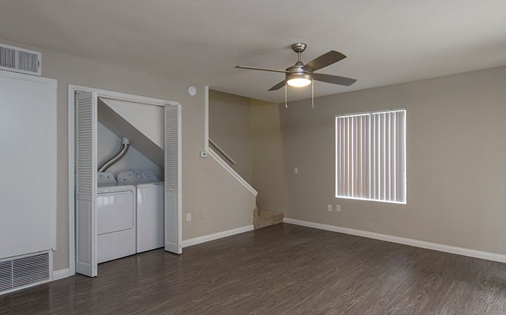 Large living room with washer/dryer and stairs to second floor at Adagio at South Coast apartments