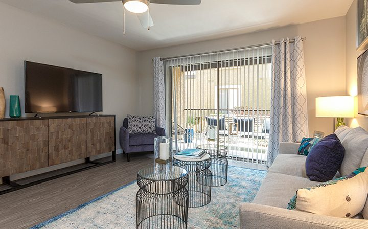 Furnished living room interior with glass door to patio at Adagio at South Coast apartments
