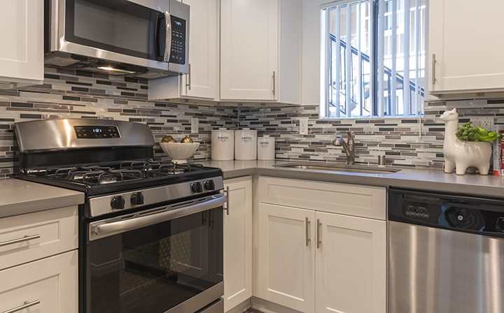 Sunny furnished kitchen with range, microwave, and dishwasher at Adagio at South Coast apartments