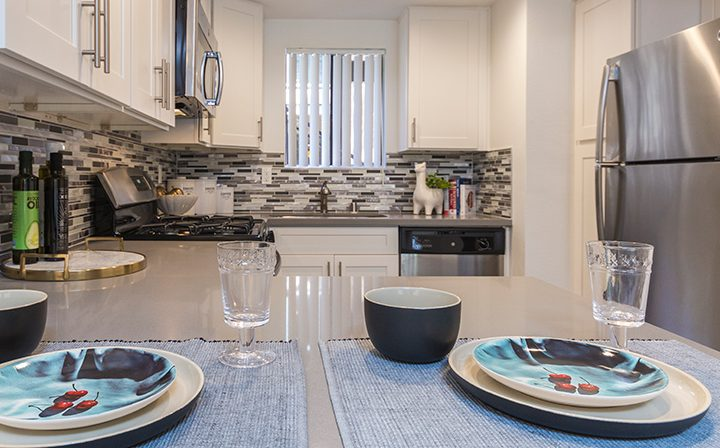 Sunny furnished kitchen with ample counter space and set table at Adagio at South Coast apartments