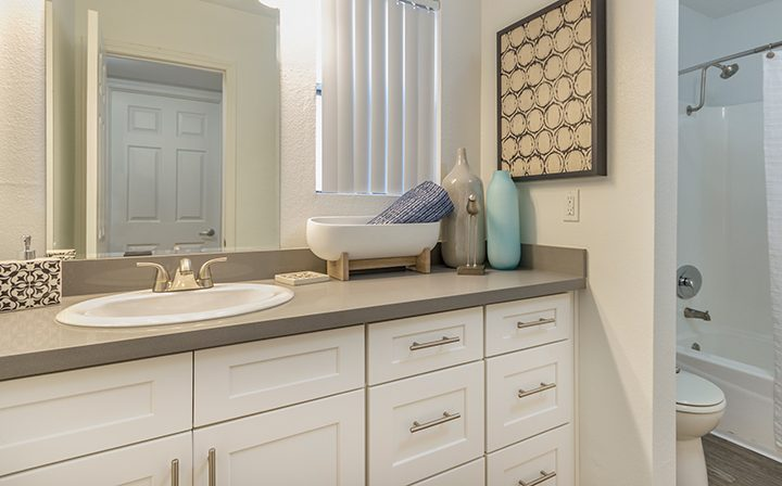 Furnished bathroom with storage space next to bathtub and shower at Adagio at South Coast apartments