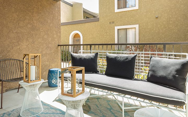 Outdoor patio with couch and chairs against textured brown walls at Adagio at South Coast apartments