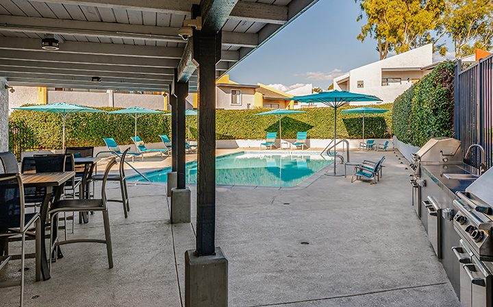BBQ grills on cement next to pool with ample seating at the Reserve at South Coast apartments