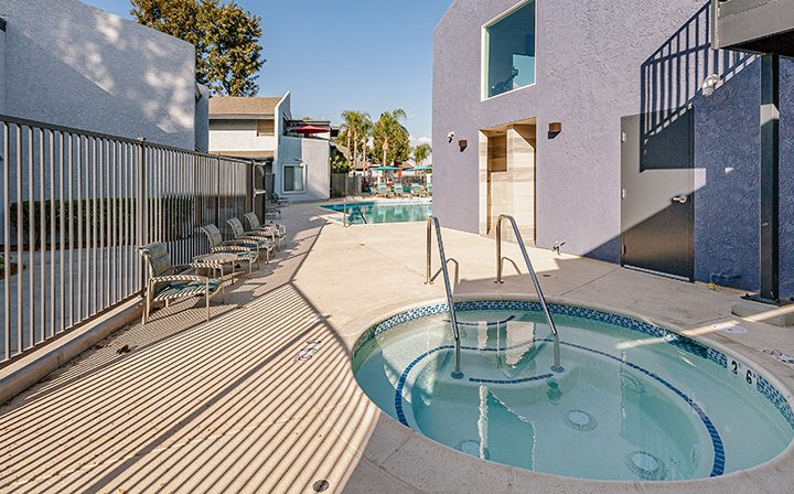 Newly renovated hot tub near pool on clear day at the Reserve at South Coast apartments