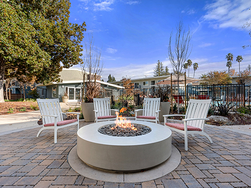 Circular outdoor fire pit with white chairs near pool at The Reserve at Walnut Creek apartments