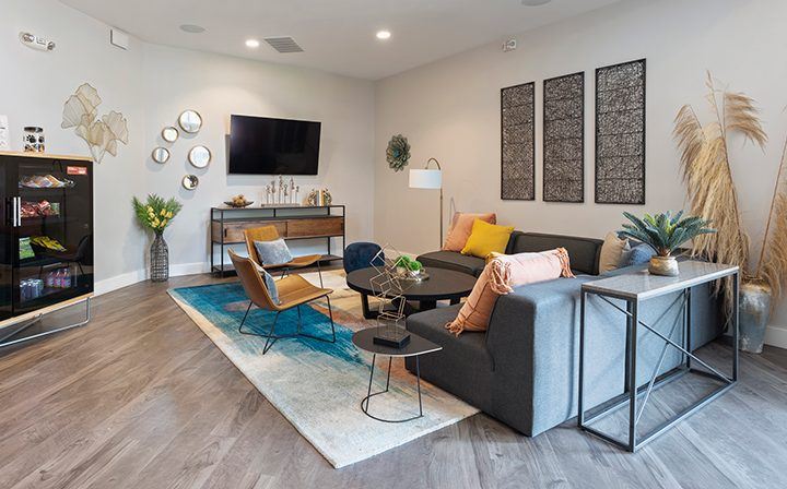 Reserve at Walnut Creek apartments clubhouse with large wall-mounted TV and comfortable seating