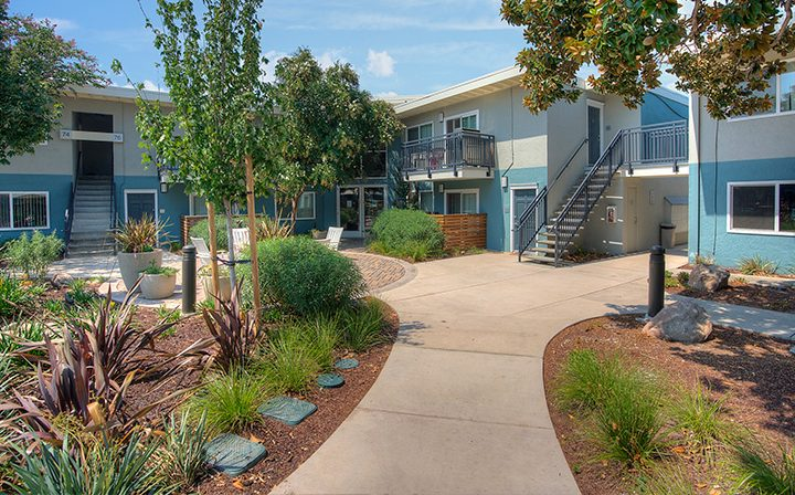 Grass and paved pathway alongside between two-story the Reserve at Walnut Creek apartment townhomes