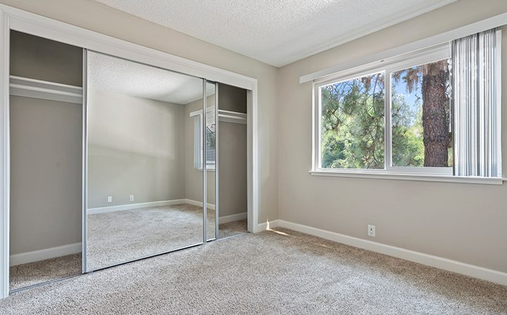 Unfurnished carpeted bedroom and mirrored closet at the Reserve at Walnut Creek apartments