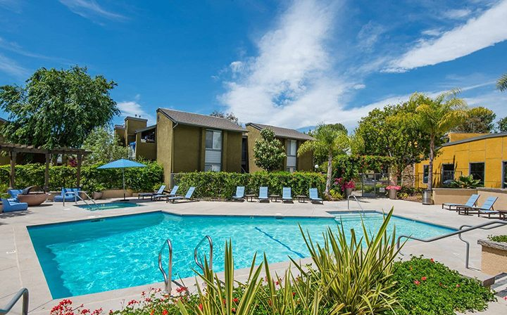 Blue seating next to large pool on a sunny day at Simi Valley apartment community River Ranch