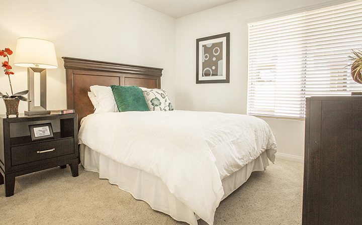 Furnished bedroom interior with bed and lamp at Simi Valley apartment community River Ranch
