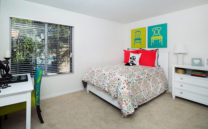Simi Valley apartments River Ranch furnished bedroom interior with bed, desk, and window view