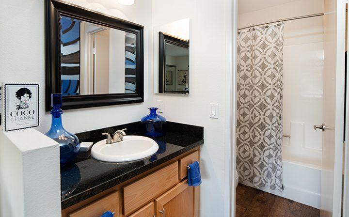 Bedroom adjacent mirror and sink next to bathroom at Simi Valley apartments community River Ranch