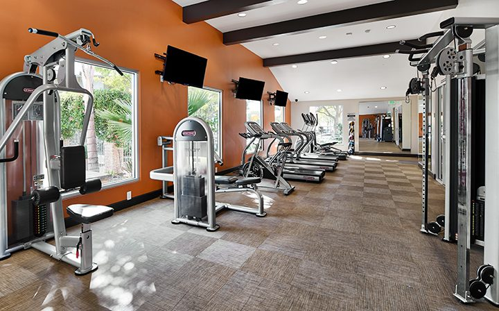 Simi Valley apartments fitness room at River Ranch with weight and cardio machines, view, and TVs