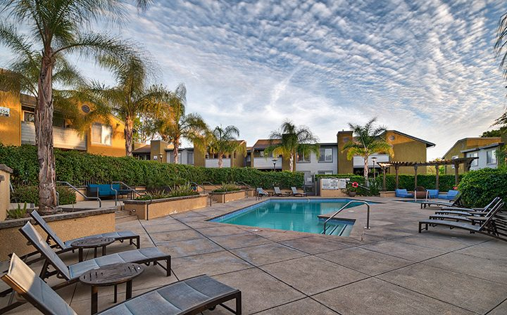 Cloudy sky above Simi Valley apartments pool at River Ranch complete with outdoor seating