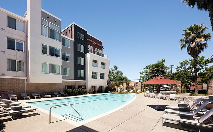 Pool on sunny day next to outdoor seating at Bridgecourt, Emeryville apartments for rent