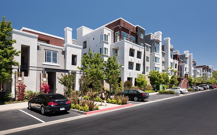 Streetside view of Bridgecourt's Emeryville apartments, with parked cars and foliage