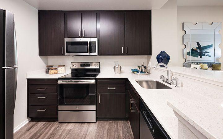 White unfurnished kitchen with dark cabinets at Bridgecourt, Emeryville apartments for rent