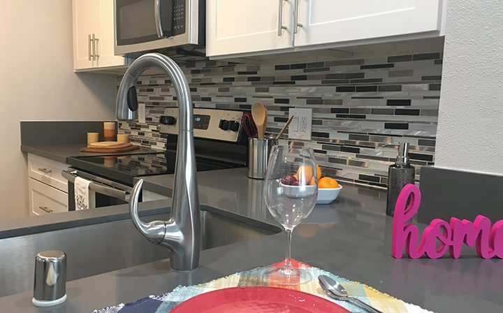 Furnished kitchen with 'home' decoration at the Bridge at Emeryville apartments community