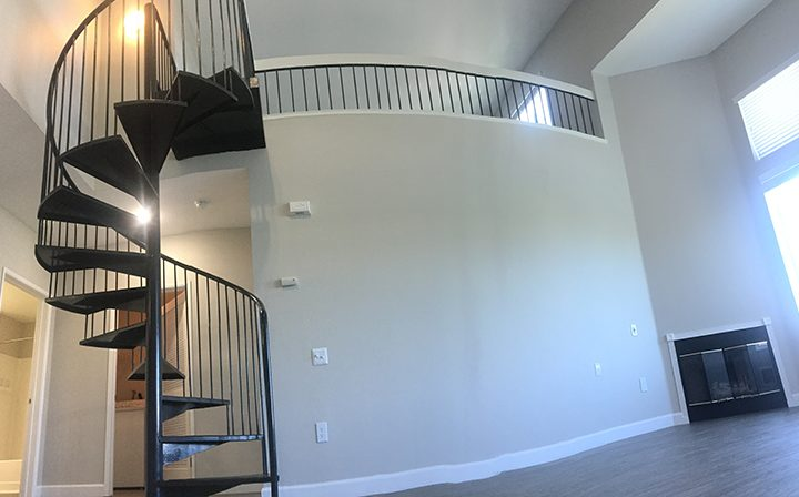 Wide angle view of apartment with spiral staircase the Bridge at the Emeryville apartments community