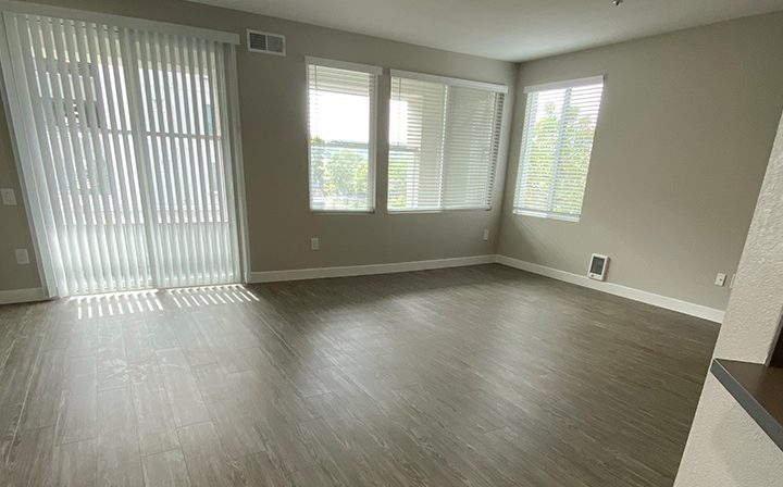 Unfurnished living room with sliding glass door at the Bridge at Emeryville apartments community