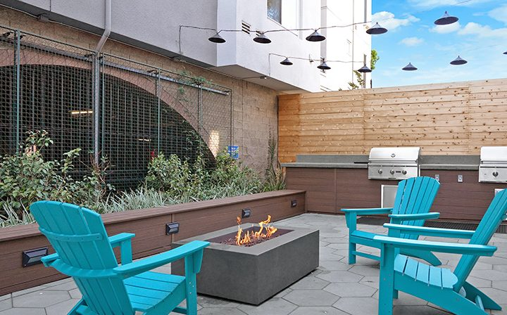 Outdoor fire pit by blue chairs at the Bridge at Emeryville apartments community