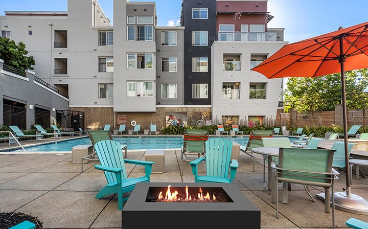 Fire pit with blue chairs at the Bridge at Emeryville apartments community pool area