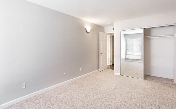 Unfurnished bedroom with carpet and mirrored closet doors at The Bridge at Walnut Creek apartments