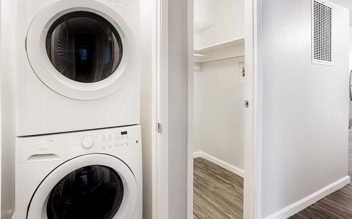 Washer/dryer combo in hallway closet next to walk-in closet at The Bridge at Walnut Creek apartments