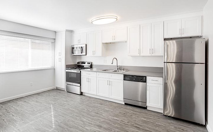 Sunny kitchen with sink, range, and fridge along one wall at The Bridge at Walnut Creek apartments