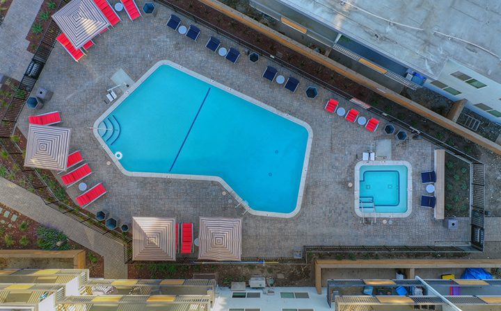 Aerial drone shot of resort-style pool, spa, and units at The Bridge at Walnut Creek apartments