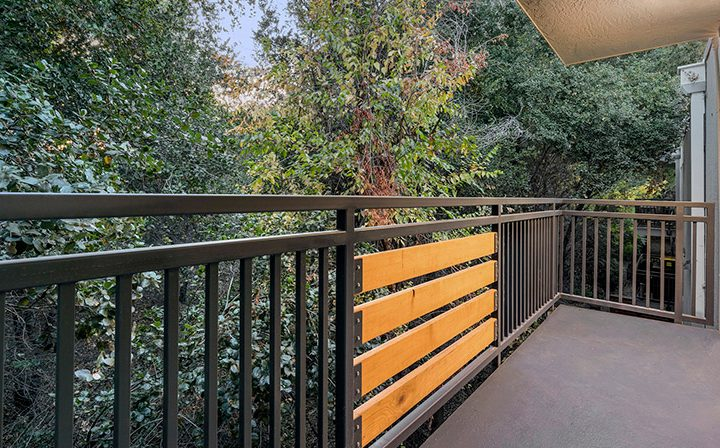 Balcony with wood and metal railing and forested view at The Bridge at Walnut Creek apartments