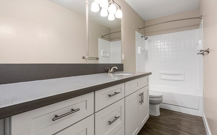Large unfurnished bathroom with many cabinets beside shower at The Bridge at Walnut Creek apartments