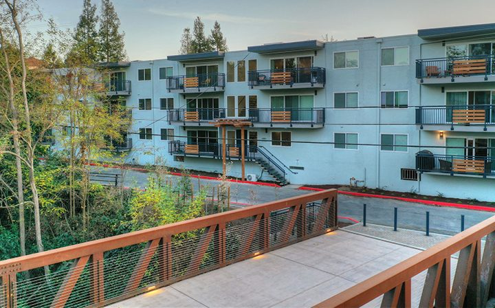 Elevated view of units on 3 levels and the eponymous bridge at The Bridge at Walnut Creek apartments