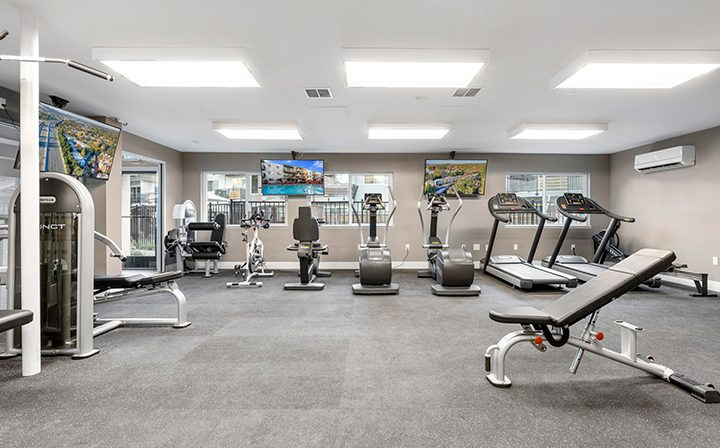 State-of-the-art fitness center with machines and large TVs at The Bridge at Walnut Creek apartments