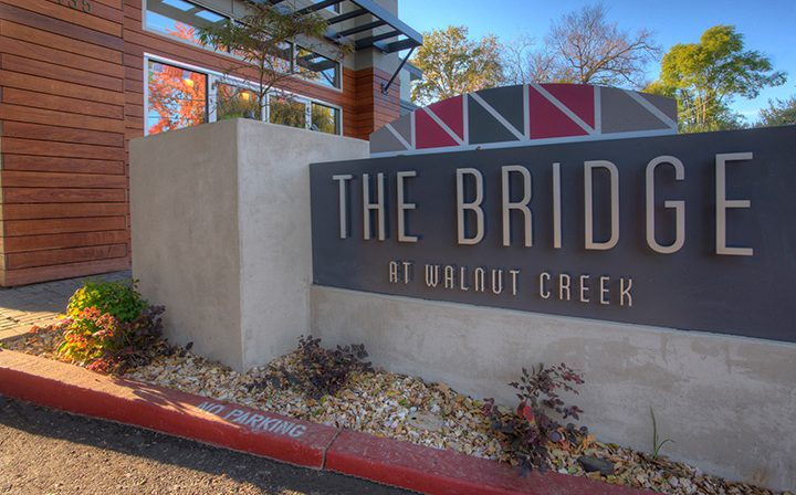 Sign for The Bridge at Walnut Creek apartments along curb outside leasing office on sunny day