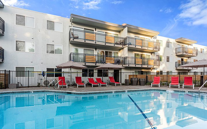 Resort-style pool with red chairs and overlooking units at The Bridge at Walnut Creek apartments
