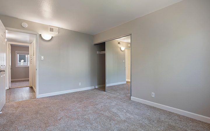 Carpeted bedroom with mirrored closet doors and long window at The Bridge at Walnut Creek apartments