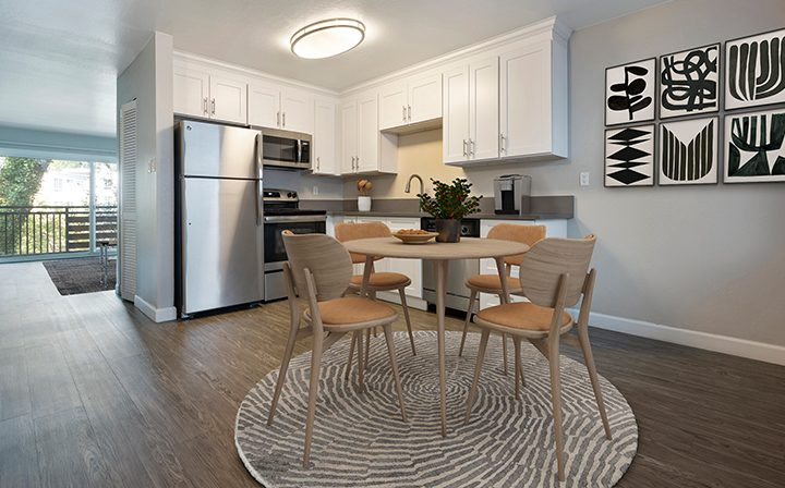 Tables and chairs in kitchen in furnished model unit at The Bridge at Walnut Creek apartments