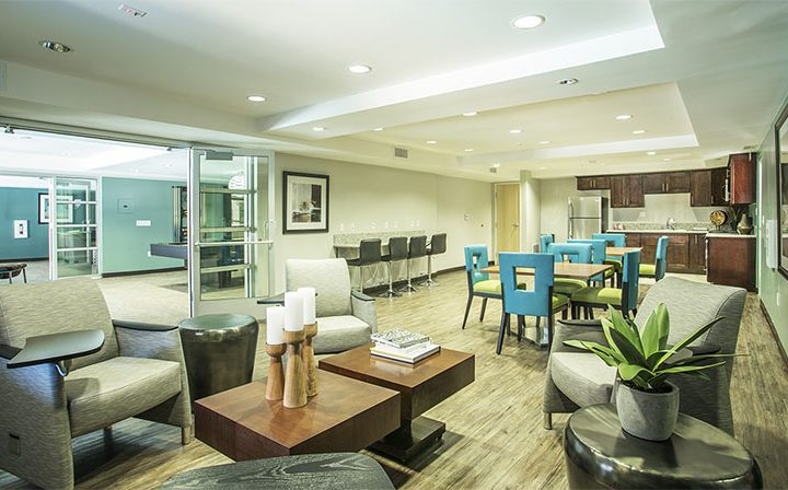 Elegant seating area with tables in the clubhouse at The Howard, apartments in Glendale