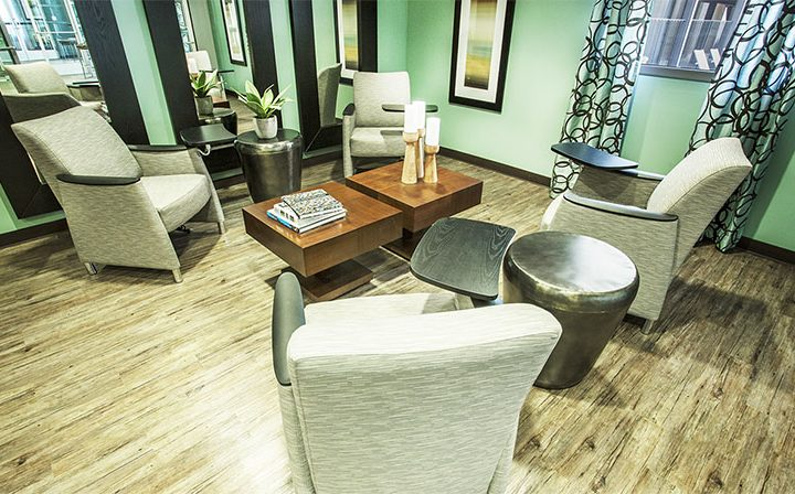 Tables and cushioned seating in the clubhouse at the Glendale apartments community The Howard