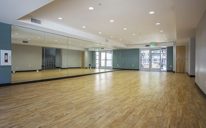 Large mirrored yoga room or fitness area at the Glendale apartments community The Howard