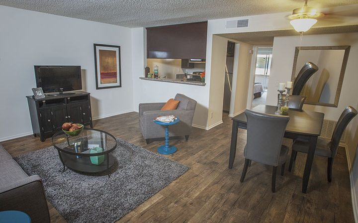 Furnished living room with kitchen visible at the Glendale apartments community The Howard