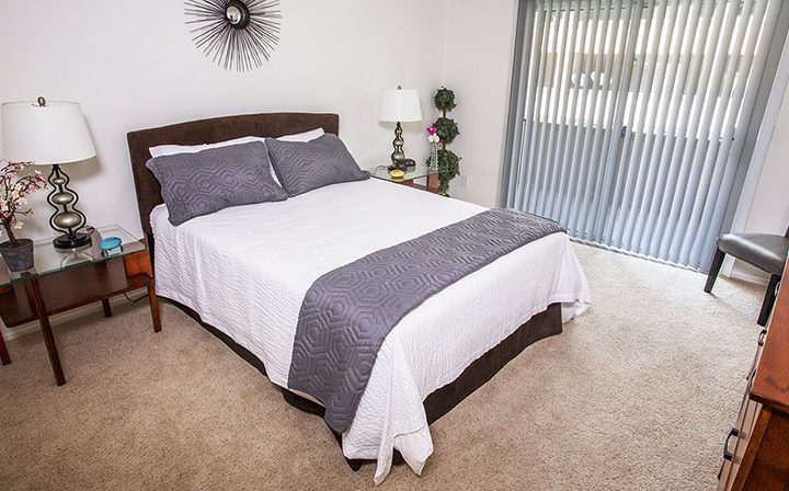 Furnished bedroom with carpet flooring at The Howard, apartments in Glendale