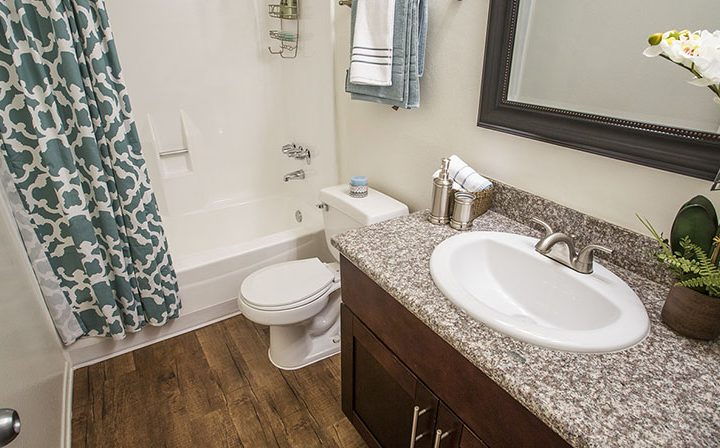 Furnished bathroom with brown cabinets and wood floor at Glendale apartments community The Howard