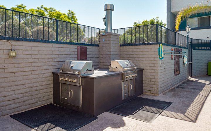 BBQ grills against a brick wall corner at the Glendale apartments community The Howard