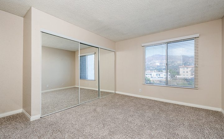 Unfurnished bedroom with carpeting and mirrored closet The Howard, apartments in Glendale