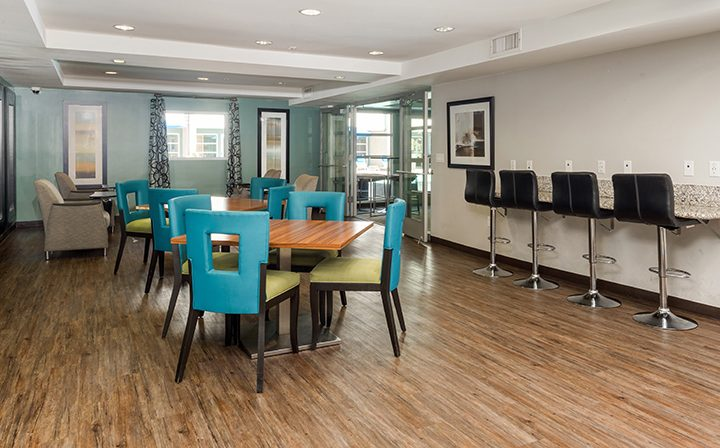 Colorful chairs on hardwood floor in the clubhouse at the Glendale apartments community The Howard
