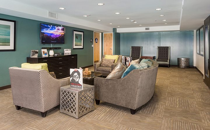 Large TV and lounge seating in the clubhouse at the Glendale apartments community The Howard